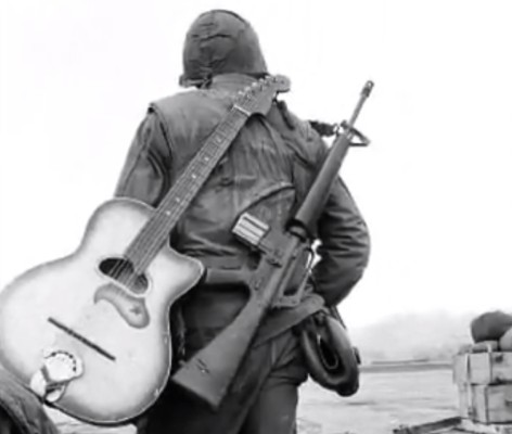 Vietnam soldier with a gun and acoustic guitar on his back